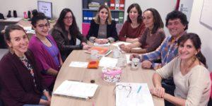 Photographie des 8 membres de l'équipe, assis autour d'une table ronde dans leur bureau. Ils sourient tous.